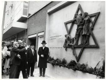 Burgemeester mr. H.A.M.T. Kolfschoten onthulde op 12 oktober 1967  het gedenkteken voor de weggevoerde Joden aan de Gedempte Gracht. V.l.n.r. de burgemeester, D. Stins (beeldhouwer), I. Zadoks (voorzitter van de Stichting Levi Lassen), en opperrabijn S. Beëri – foto Stokvis