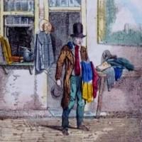Een Joodse verkoper met een hoge hoed op en een aantal kledingstukken over zijn arm staat voor zijn winkel in gedragen kleding (en andere zaken). Rechts van hem op een tafel liggen nog meer oude kleren. – ca. 1850, collectie Joods Historisch Museum
