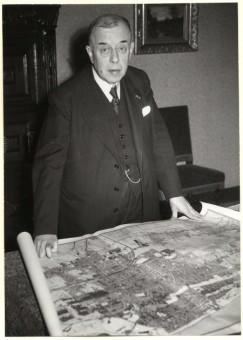 Wethouder ir. L.J.M. Feber van Volkshuisvesting en Wederopbouw met een plattegrond van Den Haag. Hij zei in 1948 in de gemeenteraad dat hij een te grote aanslag op de gemeentekas vreesde als de in Den Haag teruggekeerde Joden de achterstallige erfpacht over de oorlogsjaren niet hoefden te betalen - fotocollectie Haags Gemeentearchief