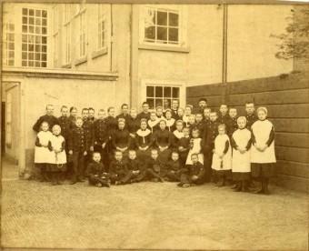 Hoogstwaarschijnlijk kinderen en personeel aan de achterzijde van het Joodse weeshuis aan de Raamstraat 45 - foto uit 1895, fotocollectie Haags Gemeentearchief