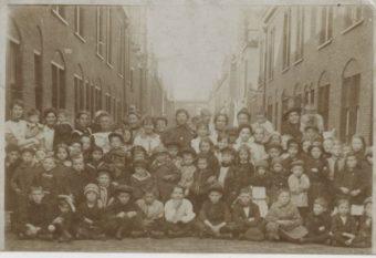 Van Ostadewoningen, een groep buurtkinderen poseert, op de achtergrond Jacob Catsstraat 65/20-65/41 - collectie Haags Gmeentearchief